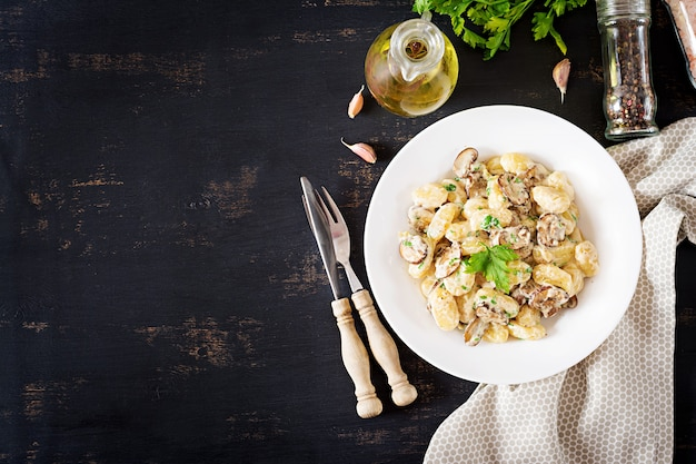 Gnocchi z grzybowym sosem śmietanowym i pietruszką, widok z góry copyspace
