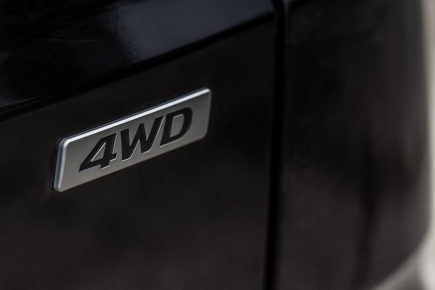 Godło 4wd na nowoczesny samochód suv szczegóły bliska widok. chromowana plakietka z napędem na cztery koła.