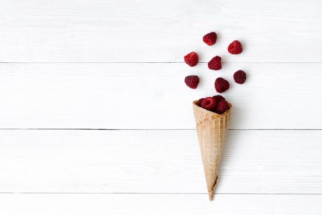 Gofra rożek z świeżymi organicznie malinowymi jagodami na białym drewnianym tle z kopii przestrzenią