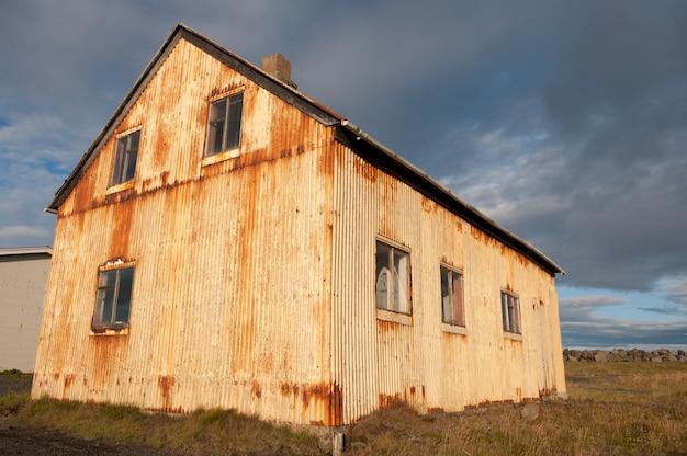 Gofrowany ośniedziały metalu mieszkanie na obszarach trawiastych pod burzowym niebem