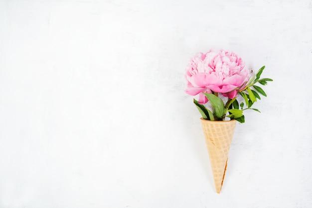 Gofrowany rożek z wystającym z niego różowym kwiatem piwonii leży po prawej stronie na zdjęciu. kreatywne zdjęcie poziome z miejsca kopiowania. widok z góry