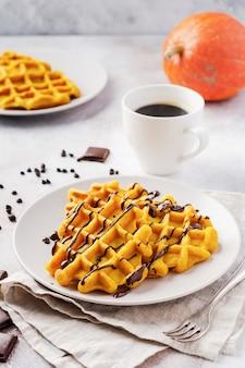 Gofry dyniowe z czekoladą i cukrem pudrem na jasnym i starym rustykalnym stole śniadaniowym