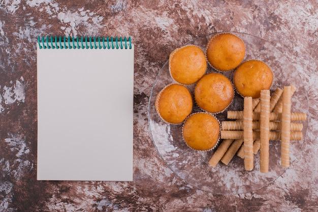 Gofry i babeczki na szklanym talerzu na marmurze z książeczką rachunków na boku