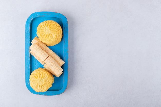 Gofry i ciasteczka na drewnianym talerzu, marmurze.