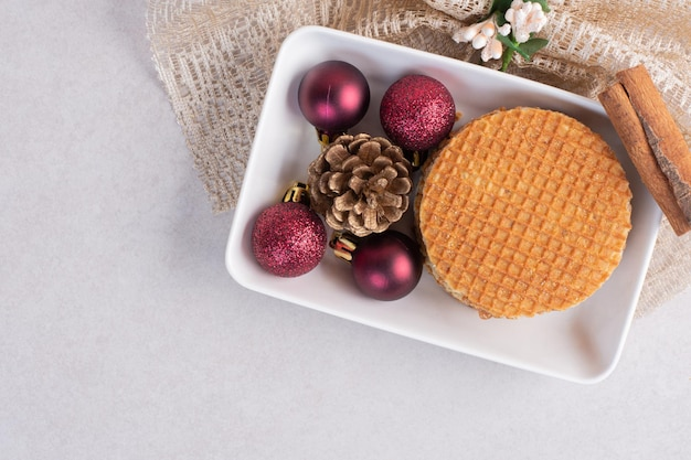 Gofry z cynamonem i świątecznymi zabawkami na białym talerzu.