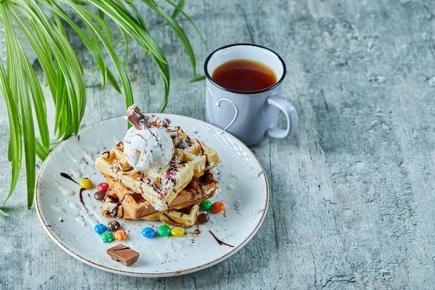 Gofry z lodami, czekoladą, kulkami czekoladowymi na białym talerzu z herbatą