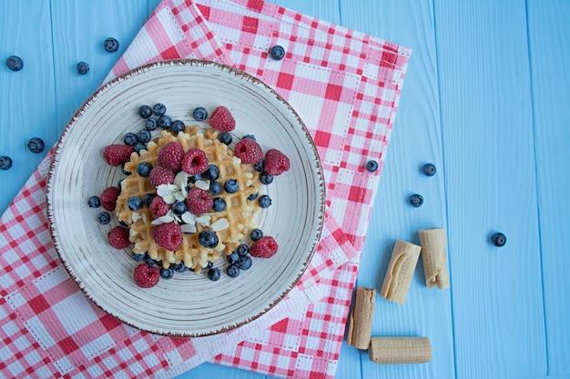 Gofry ze świeżym bananem, malinami, jagodami na śniadanie. belgijskie gofry.