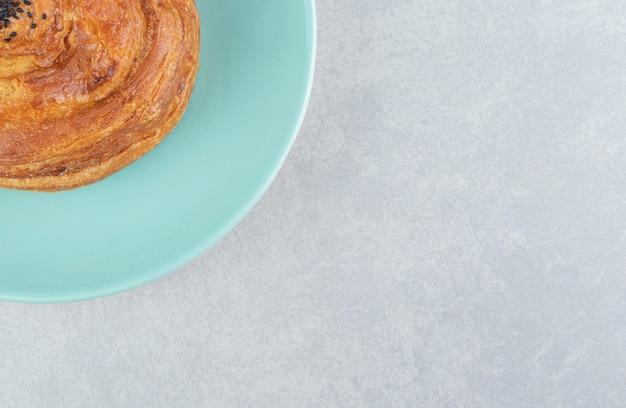 Gogal świeżego ciasta na niebieskim talerzu.