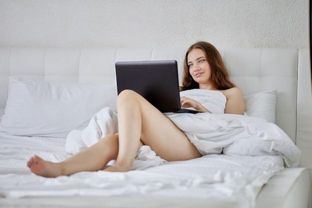 Goła kobieta w łóżku podczas telepracy z laptopem