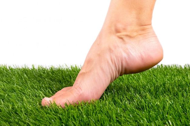 Gołą stopą dotyka zbliżenie zielonej sztucznej trawy