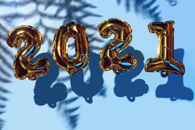 Golden christmas balls 2021. z cieniami na niebieskiej ścianie. koncepcja nowego roku.