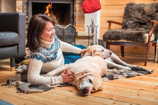 Golden labrador retrievers leżą razem z azjatką w średnim wieku na kocu przed kominkiem w wiejskim domu.
