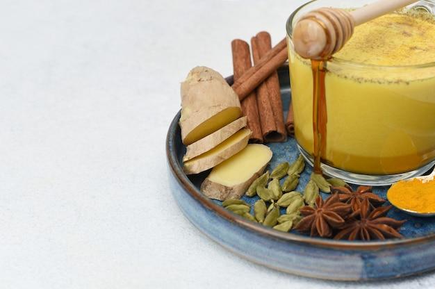 Golden milk, wykonane z kurkumy i innych przypraw. szklany kubek ze złotym mlekiem i przyprawami na jasnym tle z miejsca kopiowania.
