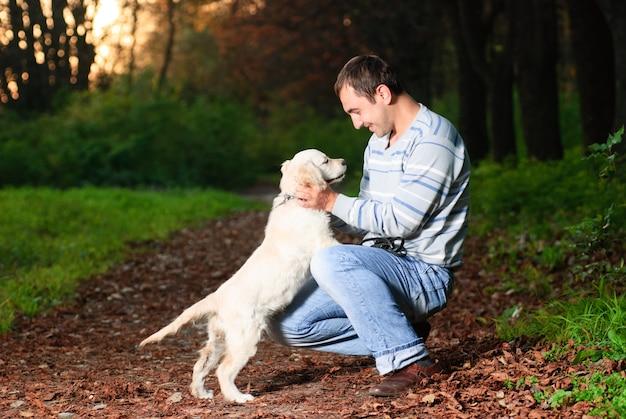 Golden retriever i człowiek bawią się w parku