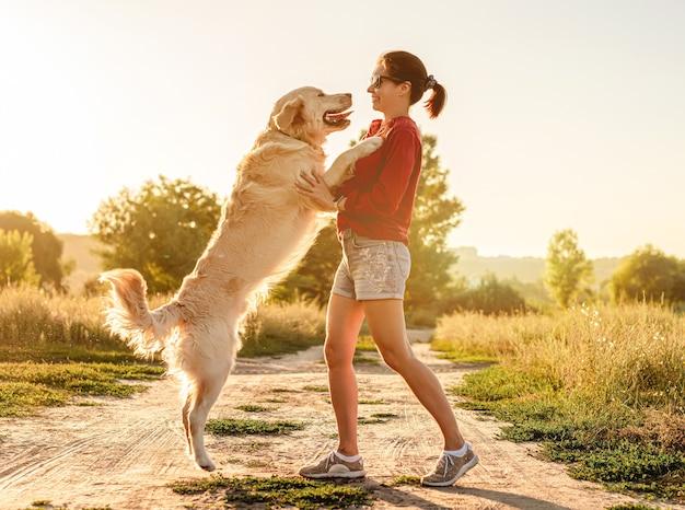 Golden retriever skoki na kobietę podczas spaceru po naturze o zachodzie słońca