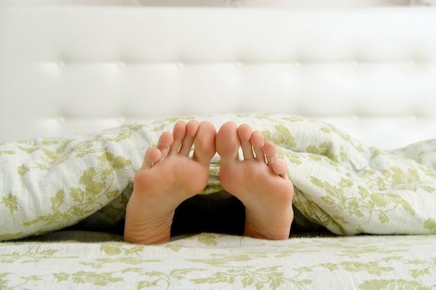 Gołe kobiece stopy z długimi palcami wystającymi spod koca