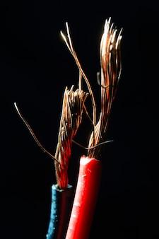 Gołe przewody miedziane w kolorze czarnym i czerwonym na ciemnym tle. makro.