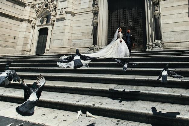 Gołębie latają przed oszałamiającą ślubną parą stojącą przed gotyckim kościołem
