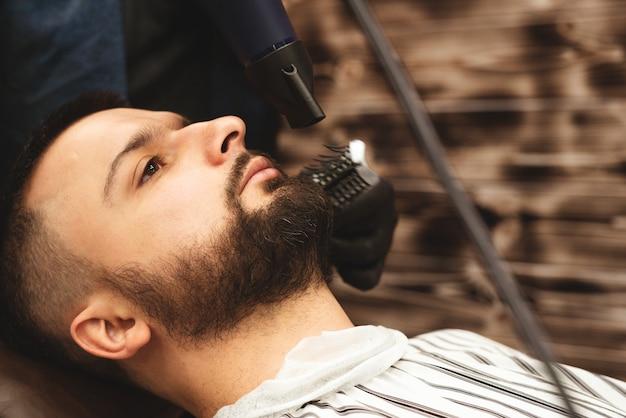Golenie brody w zakładzie fryzjerskim niebezpieczną brzytwą. pielęgnacja brody barber shop. suszenie, strzyżenie, strzyżenie brody. selektywne ustawianie ostrości.