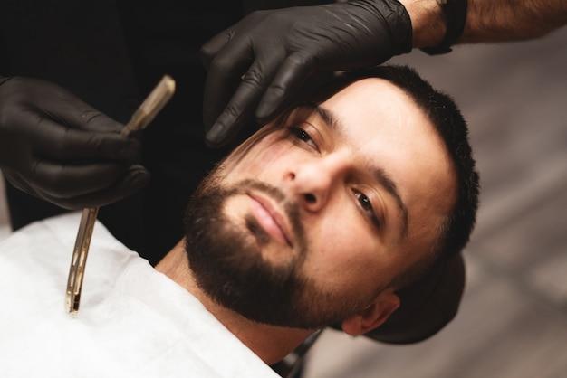 Golenie brody w zakładzie fryzjerskim niebezpieczną brzytwą. pielęgnacja brody barber shop. suszenie, strzyżenie, strzyżenie brody.