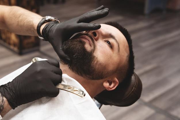 Golenie brody w zakładzie fryzjerskim niebezpieczną brzytwą.