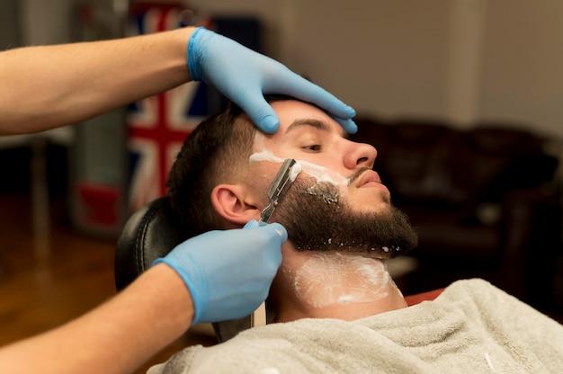 Golenie fryzjera i konturowanie męskiej brody klienta