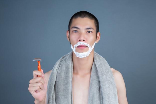 Golenie przystojnego faceta ogolonego na szaro na twarzy