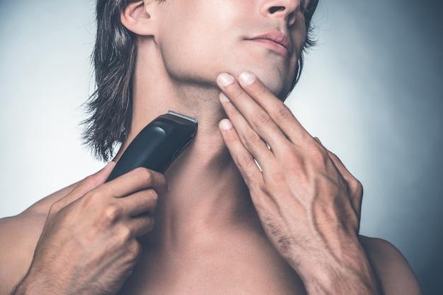 Golenie za pomocą elektrycznej maszynki do golenia. zbliżenie: przystojny młody mężczyzna bez koszuli goli się elektryczną maszynką do golenia, stojąc na szarym tle