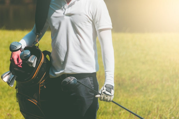 Golfiści niosą torby, które zawierają wiele kijów golfowych, gotowych do gry.