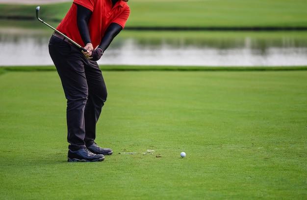 Golfiści uderzają o rozległe pole golfowe z toru wodnego o wschodzie słońca