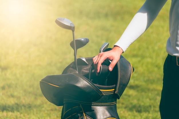 Golfiści wybierają kije golfowe.