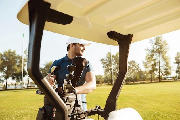 Golfista bierze kluby z torby w wózku golfowym