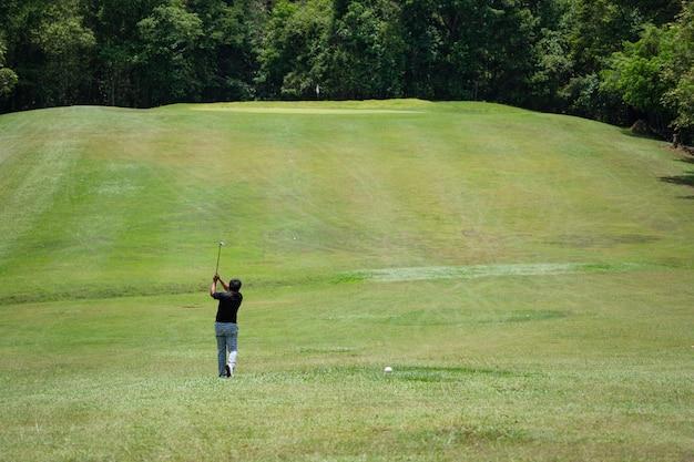 Golfista huśtawka piłka golfowa dziura na pięknym zielonym farwaterze i układ na tle lasu
