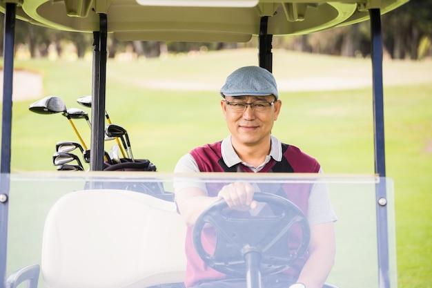 Golfista jazdy wózkiem golfowym