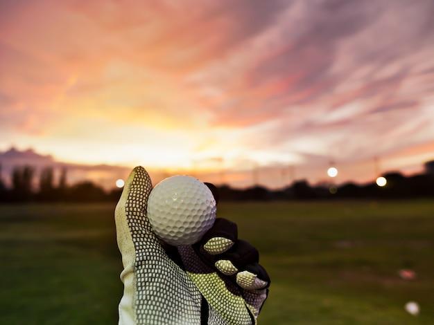 Golfista ręka jest ubranym golfową rękawiczkę i trzyma piłkę golfową na trójniku z pięknym wschodem słońca