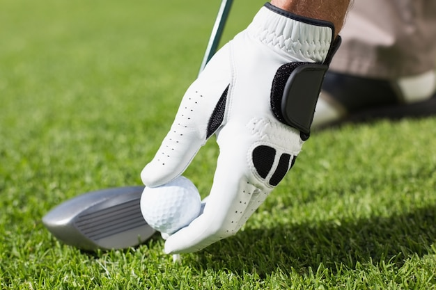Golfista umieszcza piłkę golfową na trójniku