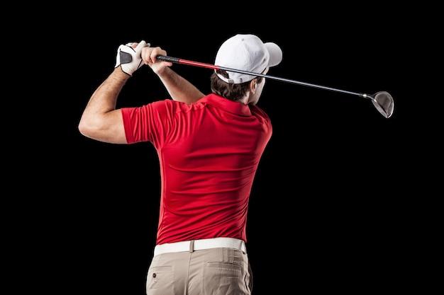 Golfista w czerwonej koszuli przy zamachu, na czarnym tle.