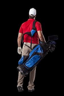 Golfista w czerwonej koszuli spaceru z torbą kijów golfowych na plecach, na czarnym tle.