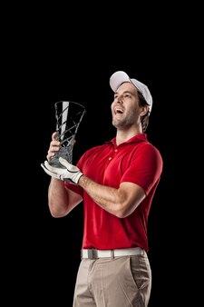 Golfista w czerwonej koszuli świętuje ze szklanym trofeum w dłoniach, na czarnym tle.