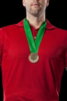 Golfista w czerwonej koszuli świętuje złoty medal na czarnym tle.