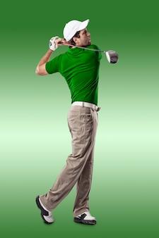 Golfista w zielonej koszuli huśtawka, na zielonym tle.