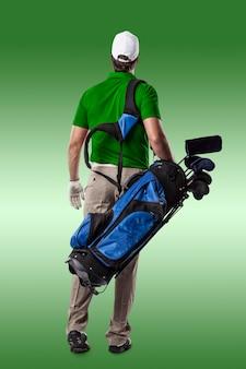 Golfista w zielonej koszuli spaceru z torbą kijów golfowych na plecach, na zielonym tle.