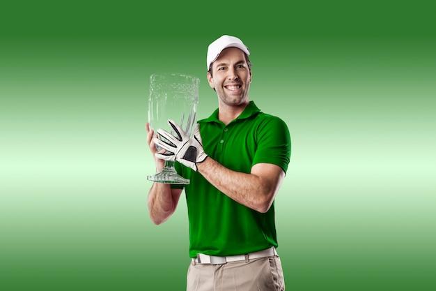 Golfista w zielonej koszuli świętuje z trofeum szkła w dłoniach, na zielonym tle.