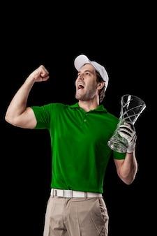 Golfista w zielonej koszuli świętuje ze szklanym trofeum w dłoniach, na czarnym tle.