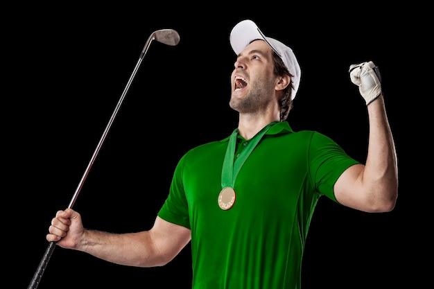 Golfista w zielonej koszuli świętuje ze złotym medalem, na czarnym tle.