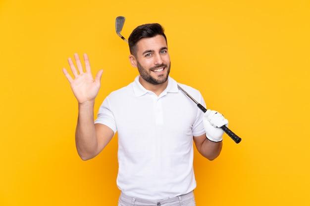Golfisty gracza mężczyzna nad odosobnioną kolor żółty ścianą salutuje ręką z szczęśliwym wyrażeniem