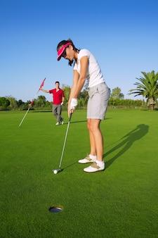 Golfowa kobieta gracza zieleni kładzenia dziury piłka golfowa