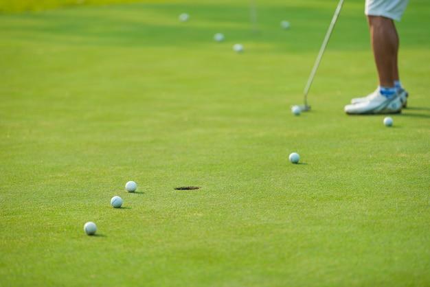 Golfowy gracz stawia piłkę golfową