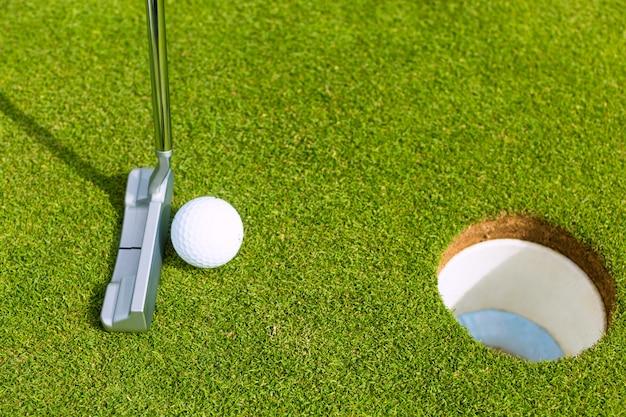 Golfowy gracz stawia piłkę w dziurze