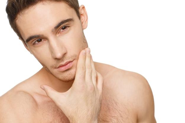 Golić się czy nie? strzał studio zbliżenie człowieka dotykając jego twarzy myśli do golenia